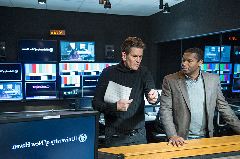Two faculty members talking in a TV production room