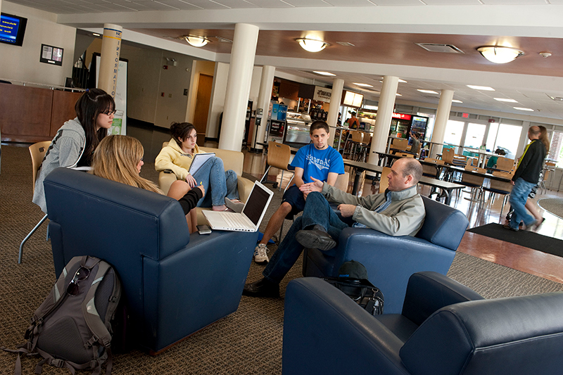 Faculty in discussion with students in a lobby