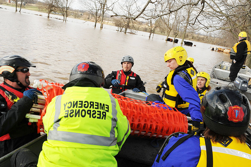 Emergency personnel pulling a boat out of a river