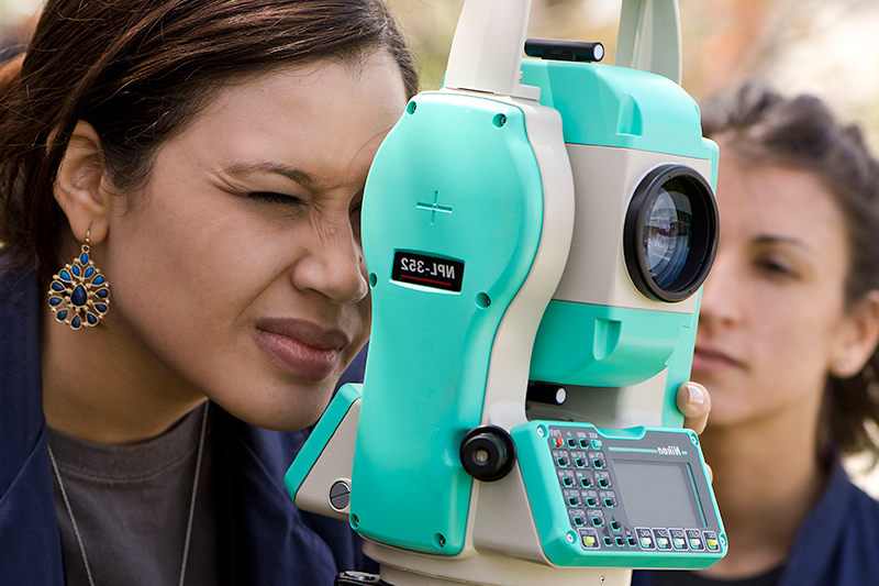Woman looking through surveying equipment